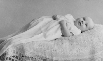 cute smiling baby in white christening gown  lying on bed