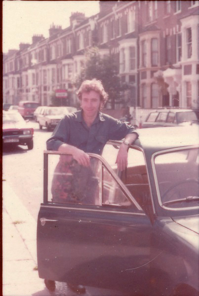 Martin Lovis standing by  his  Fiat 124 Sport Coupe car outsdie London flat before sale of both the pay off debts.