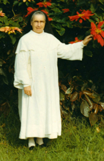 nun dressed in white habit and black veil standing in garden touching a big red flower. Probably taken in South Africa.