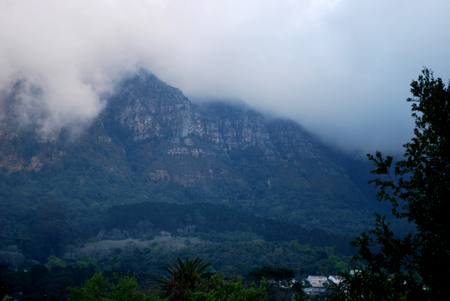 Mountain buttresses almost completly covered in heavy rain clouds and the forest below is covered in a low hanging mist.