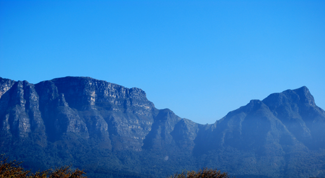 Panoramic distant view of Table Mountain east side Devil's Peak under blue green haze on a clear sunny day with clear blue sky overhead.