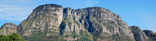 The six main buttresses of Table Mountain east side seen from a distance on a clear sunny day under blue sky  with some high white clouds.