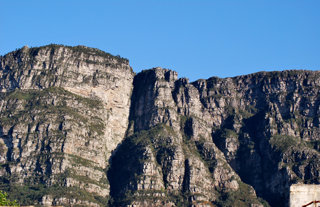 Clear light view of Fernwood and Protea buttresses on clear sunny day with dark shadows and craggy sandstone layers clearly defined showing undulations in the formation of the layers.