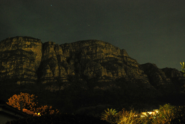 Moonlight reflected on buttresses of Table Mountain with  red and white stars above and tiny house in the distance at the foot of the mountain with their house lights on.
